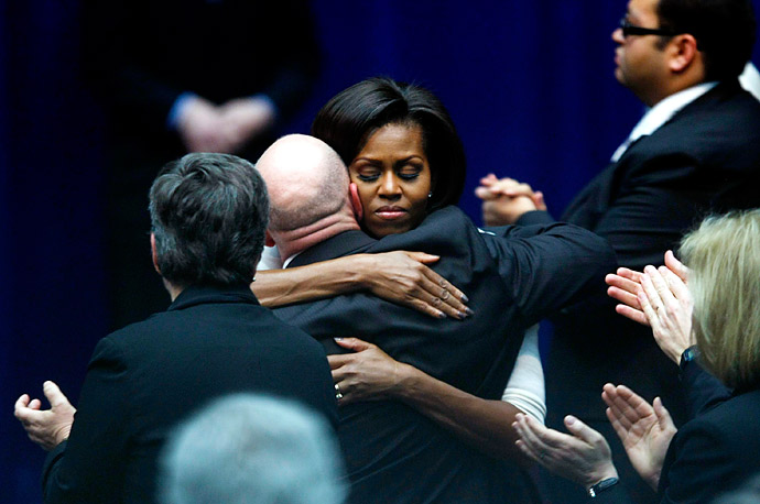 U.S. first lady Michelle Obama hugs Congresswoman Gabrielle Gifford's husband, NASA shuttle commander Mark Kelly, during President Barack Obama's address at the