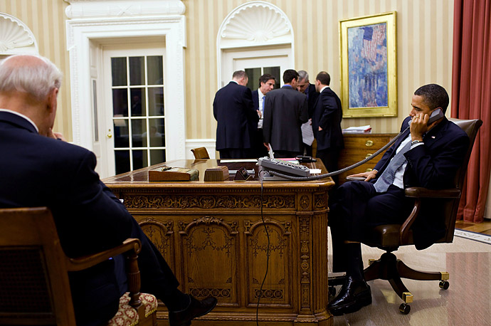 President Barack Obama talks on the phone with President Hosni Mubarak of Egypt as Vice President Joe Biden, left, and the President's national security team listen in the Oval Office January 28,