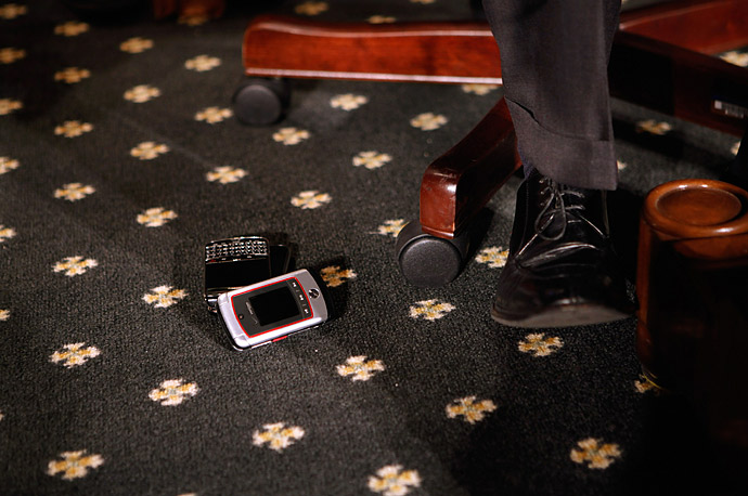 Treasury Secretary Timothy Geithner's Blackberry and mobile phone sit on the floor next to him as he prepares to testify before the Senate Finance Committee on Capitol Hill.