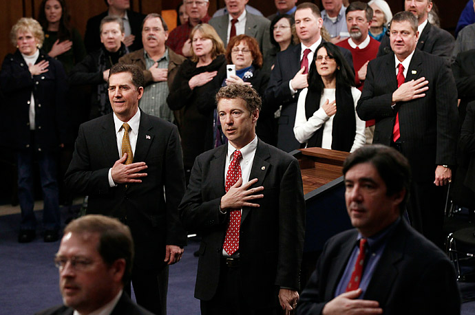 Sen. Jim DeMint (R-SC) (L) and U.S. Sen. Rand Paul (R-KY) (R) join Tea Party supporters in saying the Pledge of Allegiance during the first meeting of the U.S. Senate Tea Party Caucus on Capitol Hill.