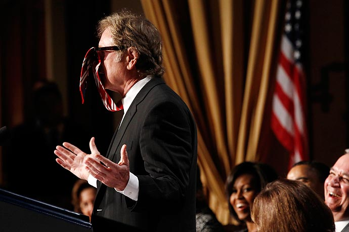 Film maker and writer Randall Wallace receives laughter as he tells a story involving his necktie getting caught up over his sunglasses during the National Prayer Breakfast in Washington.