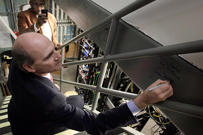 Singer James Taylor, a 2010 National Medal of Arts recipient, signs his name in an area that was once the White House indoor swimming pool.