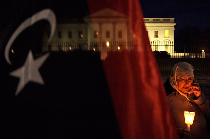 Libyan-American Kadija Sharif stands outside the White House with a pre-Gaddafi era flag during a vigil to support those opposing Gaddafi's rule.