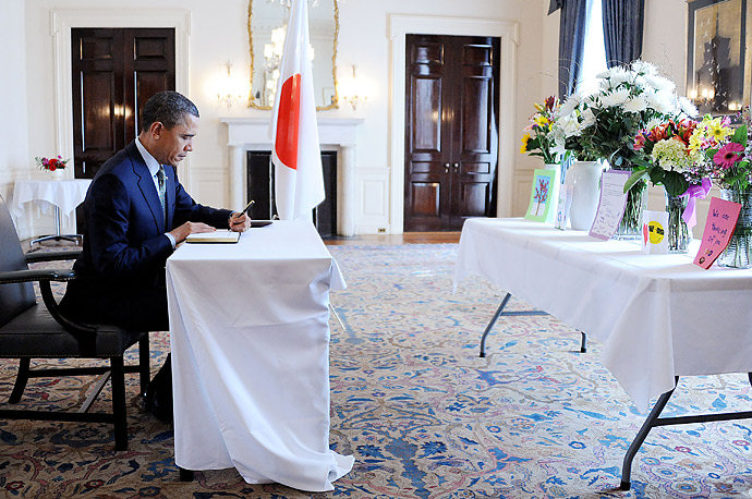 President Barack Obama sits at a desk to write a note while making a surprise visit to the Japanese Embassy in Washington, DC.