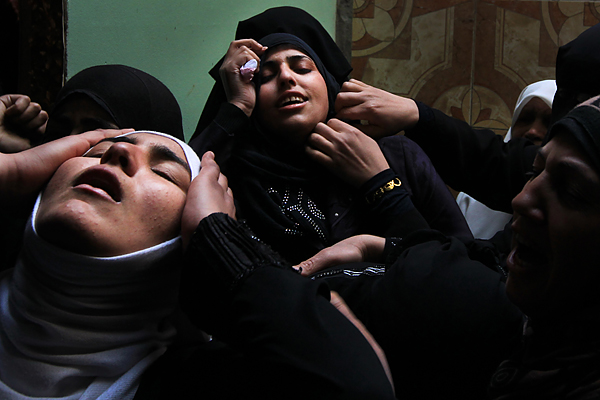 Relatives of Islamic Jihad militant Mohammed Daher, who was killed the night before in an Israeli strike, mourn during his funeral in Gaza City on March 13, 2012.