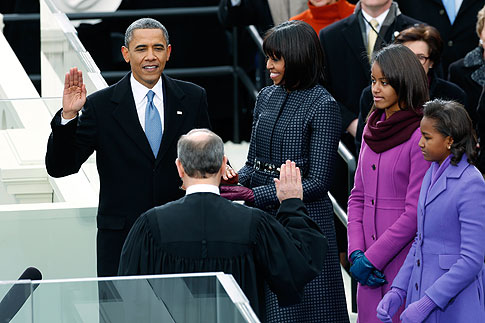 image: U.S. President Barack Obama (L) is sworn in by Supreme Court Justice John Roberts, as first lady Michelle Obama and her daughters, Sasha (R) and Malia, look on during inauguration ceremonies in Washington, January 21, 2013.