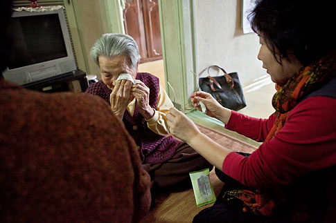 Lee Geum-sook, a volunteer for elderly people, right, tries to comfort Yoon Jeom-do, an 89-year-old elderly woman who lives alone in an apartment in Nowon district in Seoul, as she sheds tears, South Korea, Oct, 18, 2012.