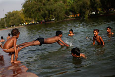 Indian children cool off in a lake on a hot afternoon in New Delhi, India, May 22, 2013.