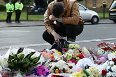 A man contemplates at a scene where flowers lay, outside Woolwich Barracks on May 23, 2013 in London.