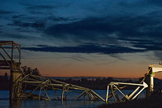 A lone helicopter leaves the scene as night falls after the collapse of the Skagit River Bridge which includes all lanes of US Interstate 5 Bridge in Mount Vernon, Washington, USA, 23 May 2013.