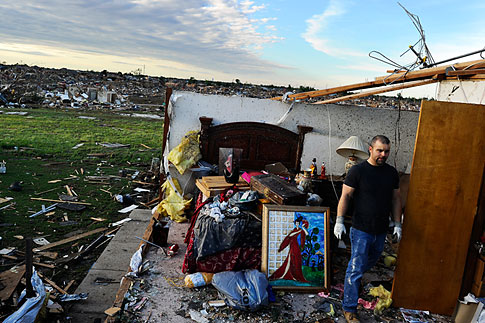 A man salvages belongings from what left of a bedroom of his tornado devastated home on May 21, 2013 in Moore, Okla.