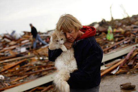 May 21, 2013. June Simson embraces her cat Sammi after she found him standing on the rubble of her destroyed home in Moore, Okla.