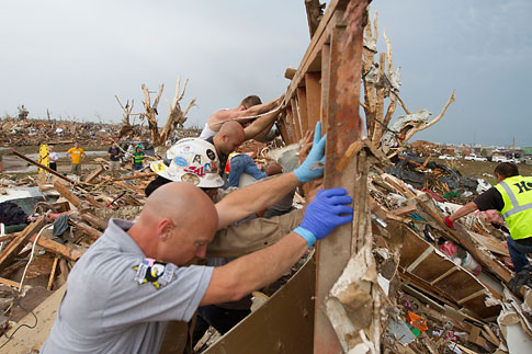 Rescuers dig out a house after a tornado in Moore, Okla., on May 20, 2013.
