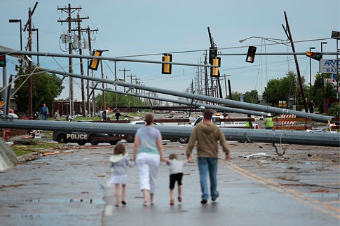 Downed utility poles block the road as a family walks south on Sante Fe Avenue at SW 19th Street after yesterday's deadly tornado on May 21, 2013 in Moore, Okla.