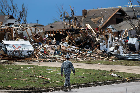 A soldier walks past the wreckage left when a tornado moved through Moore, Okla., May 21, 2013.