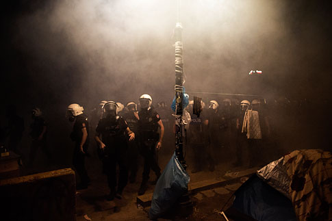 Under the cover of a cloud of tear gas Turkish riot police officers arrive to chase out demonstrators and to dismantle the tent camp set up by demonstrators in Gezi Park in Istanbul on June 15, 2013.