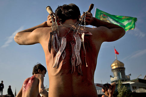 An Afghan Shi'ite beats himself with chains and blades in a ritual ahead of the Ashura holiday outside the Abul Fazel Shrine in Kabul, Afghanistan, Nov. 10, 2013.