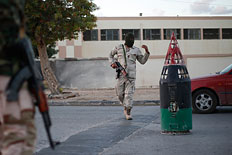 Members of the Libyan army stand guard along a street following yesterday's clashes in Benghazi November 26, 2013.