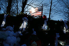 Image: A flag that bears the names of the dead flies over a makeshift memorial in Sandy Hook, after the Dec. 14 shooting tragedy when a gunman shot dead 20 students and six adults at Sandy Hook Elementary, in Newtown, Conn., on Dec. 28, 2012.