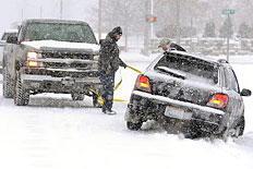 A good samaritan helps pull a motorist from the ditch as a snow plow passes on 32nd Street in Paducah, Ky., as snow fall, Dec. 6, 2013.