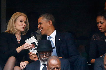 President Obama shares a laugh with Danish Prime Minister Helle Thorning-Schmidt during a memorial service for late South African President Nelson Mandela in Johannesburg, Dec. 10, 2013.