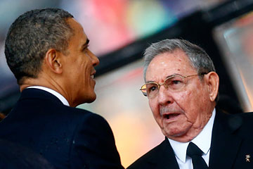 U.S. President Barack Obama greets Cuban President Raul Castro before giving his speech at the memorial service for late South African President Nelson Mandela at the First National Bank soccer stadium,Johannesburg Dec. 10, 2013.