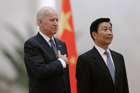 Chinese Vice President Li Yuanchao and U.S. Vice President Joe Biden listen to their national anthems during a welcoming ceremony inside the Great Hall of the People in Beijing, Dec. 4, 2013.