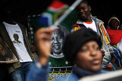 People holding South African flags and portraits of late South African President Nelson Mandela take part in a retransmission of the memorial service for Mandela, at the Orlando Stadium in Soweto on Dec. 10, 2013.