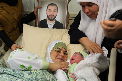 Palestinian mother Dala, looks at her new born son as she lays under a photograph of her imprisoned husband Amer al-Zein, at the al-Arabi hospital in the northern Palestinian West Bank city of Nablus, on Aug. 13, 2012.