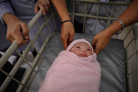 Nurses stand around a newborn baby lying in a trolley at a hallway inside a maternity ward in Karachi Oct. 25, 2011.