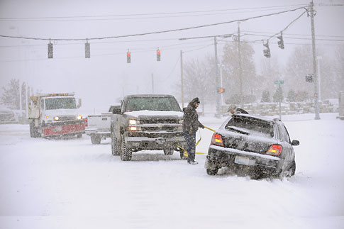 A good samaritan helps pull a motorist from the ditch as a snow plow passes on 32nd Street in Paducah, Ky., as snow fall Dec. 6, 2013.