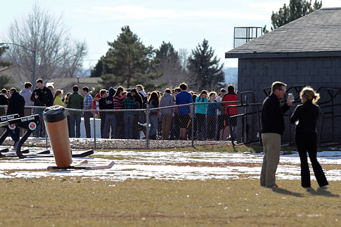 Students, school officials and public safety huddle outside Arapahoe High School in Centennial, Colo., Friday, Dec. 13, after a shooting at the school.