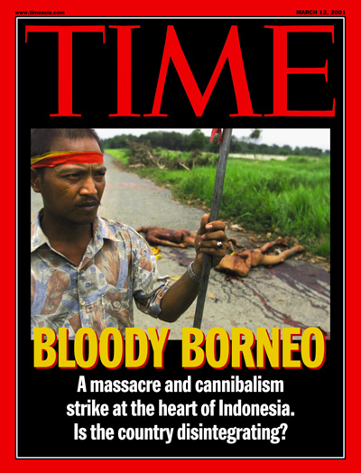 An Indonesian man holding a staff guards a cluster of mutilated bodies on a road in Kalimantan
