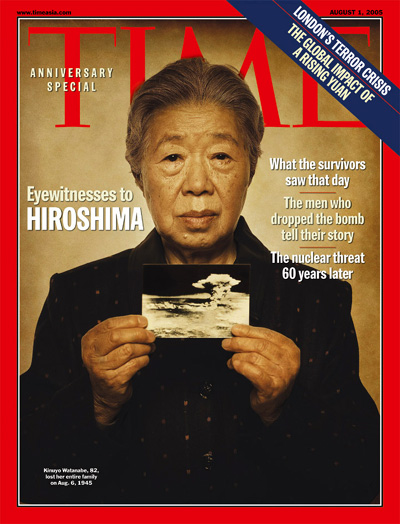 A survivor of Hiroshima holds a picture of the mushroom cloud resulting from the bomb.