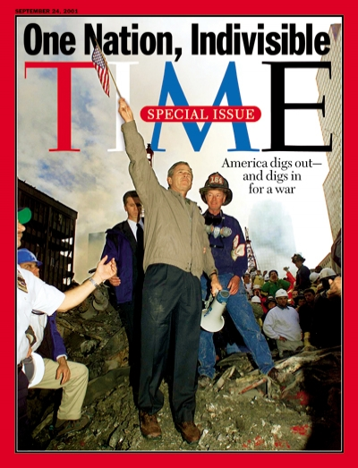Photograph of George W. Bush waving an American flag from the rubble at Ground Zero.