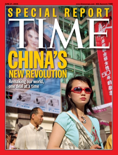Picture of a Chinese woman wearing sunglasses with billboards behind her.