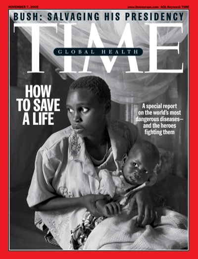 A photo of an African woman holding a baby in front of mosquito netting.