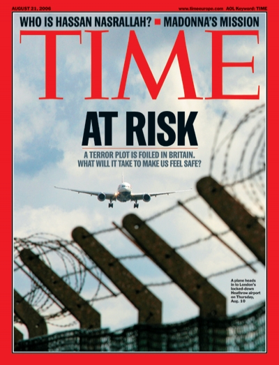Photo of barbed wire in the foreground and an airplane beginning to land in the background.
