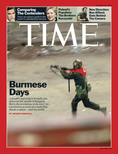 A photo of a Burmese Army man wielding a gun while running down a street.