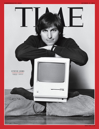 A young Steve Jobs poses with a Mac computer on his lap