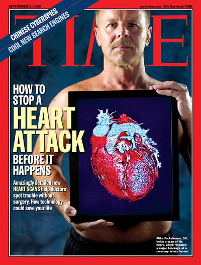 A man holding a diagram of a human heart in front of his bare chest.