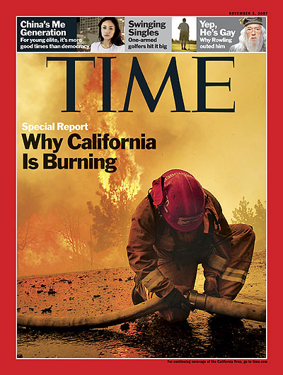 Photo of a fire fighter kneeling to connect a hose with the fire blazing behind him. Photograph by Robert Gauthier &#151; Los Angeles <span style='font-style: italic'>Times</span>