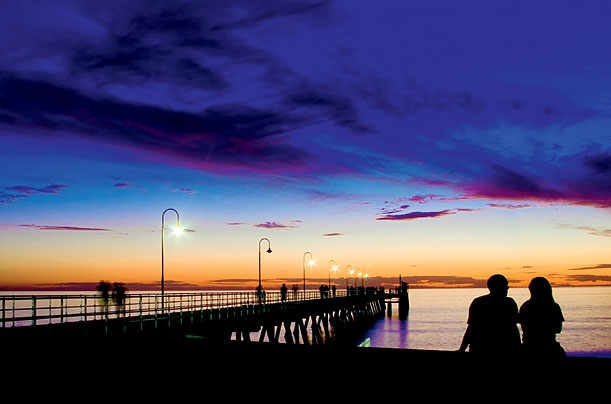 A jetty, a sunset and a couple