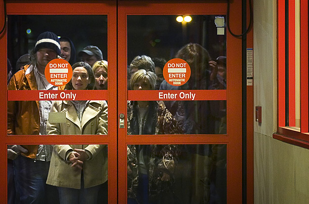 Customers stare through the doors at Target in Texarkana, Texas, before being allowed to shop. Store management said they saw over 500 customers in the first hour.