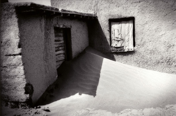 Sand drifts pile up against a mud brick house in Inner Mongolia