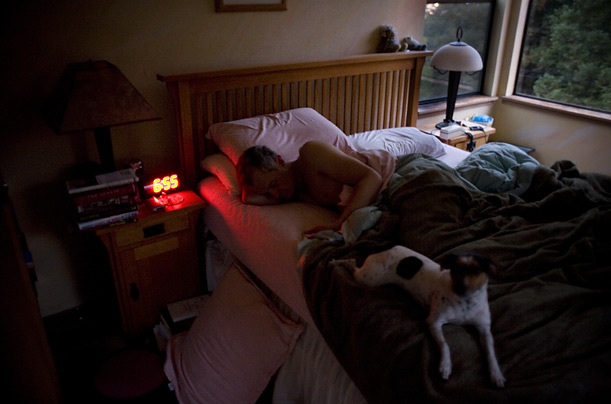 Snapshot of America Day in the Life Craig Tyler, who works at home, sleeps alongside his dog Ke-Ke. His wife Nancy is already awake and preparing to leave the house.
