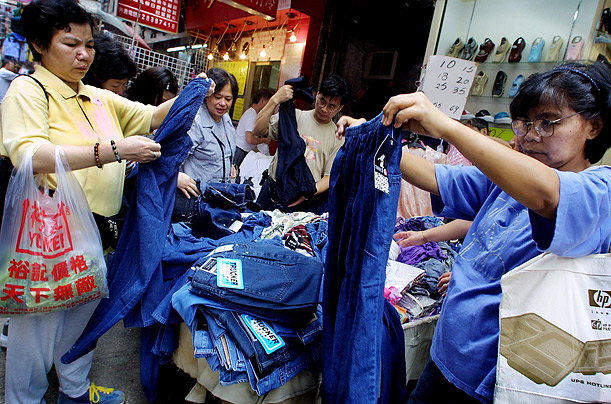 Shoppers examine jeans at bargain table on the street. Analysts estimate that the sales of jeans worldwide amounted to over 15 billion dollars in 2006.