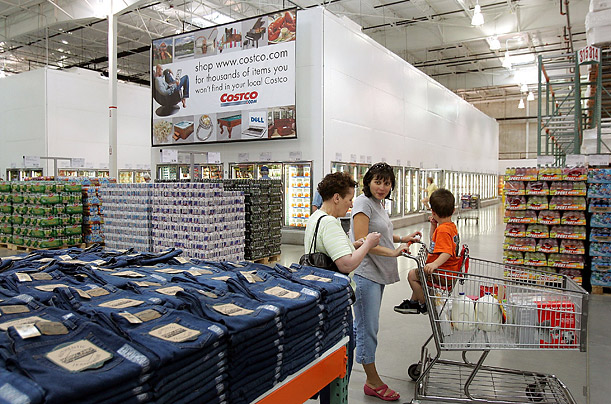 Shoppers pause next to a display at Costco. Jeans have progressed from their humble origin as a sturdy pant for workers to become a worldwide wardrobe staple.