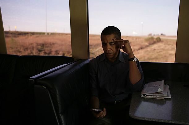 Senator Barack Obama reviews messages on his Blackberry during a morning briefing as his campaign bus travels through Iowa.