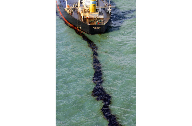A black stream of crude oil leaks from the Hong